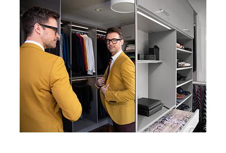 Fashion stylist Brad Goreski admiring his custom master closet by California Closets