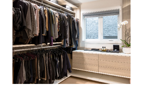 Clothes hanging on closet rods inside custom closet | California Closets