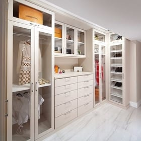 Custom white luxurious walk-in closet displaying valuable clothing